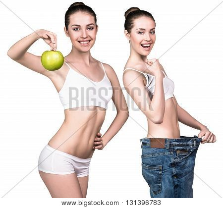 Woman became skinny and wearing old big jeans and holds green apple isolated on white