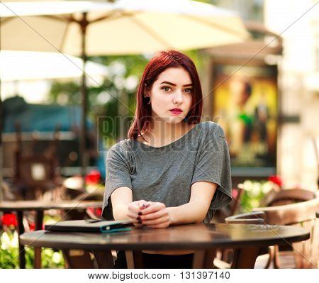 Beautiful girl at the table in a summer city cafe with tablet