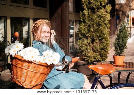 Cheerful beautiful young woman with bicycle writing in notebook and smiling on the bench outdoors