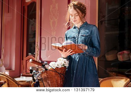 Beautiful young woman with bicycle standing and reading a book outdoors