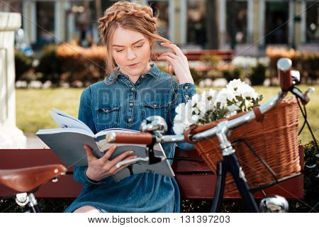 Pensive attractive young woman with bicycle sitting on the bench in park and reading magazine