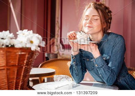 Happy cute young woman eating sweet tasty cupcake in outdoor cafe