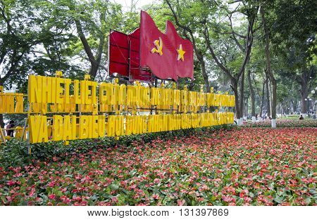 Hanoi, Vietnam - May 21, 2016: Vietnamese flag along with communist flag and a communicational message from the party and government in a floral garden at the bank of Hoan Kiem (Sword) lake.