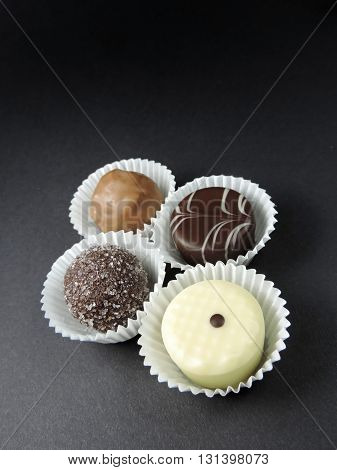 Delicious chocolate truffles, isolated on black background