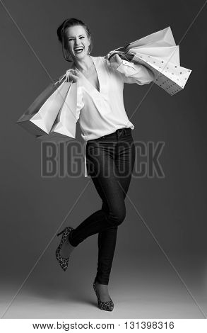 Full Length Portrait Of Smiling Elegant Woman With Shopping Bags