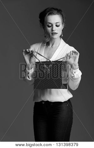 Woman Looking Inside Shopping Bag Against Grey Background