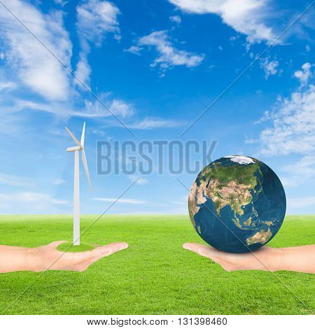 Green Earth concepthand holding wind turbine and earth against green field and blue sky background.Elements of this image furnished by NASA