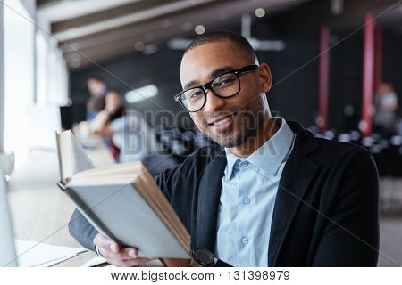 Handsome young business man reading a book at his desk in the office