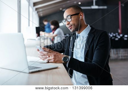 Stylish businessman typing a message using smartphone at the office