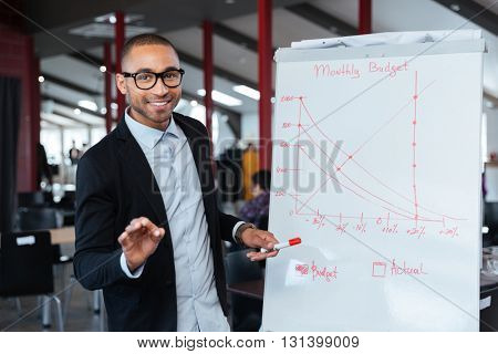 Smart businessman presenting monthy budget using flipchart