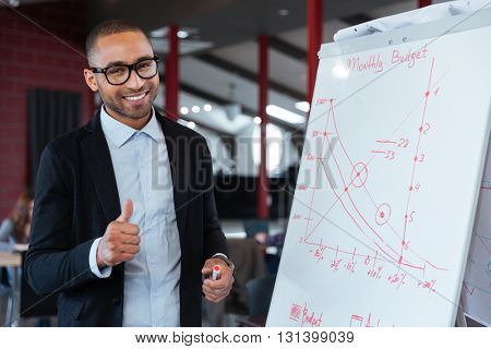 Happy businessman showing ok sign at the flipchart in the office