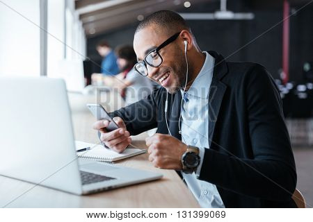 Smilling cheerful businessman texting message on the smartphone in front of the laptop in the office
