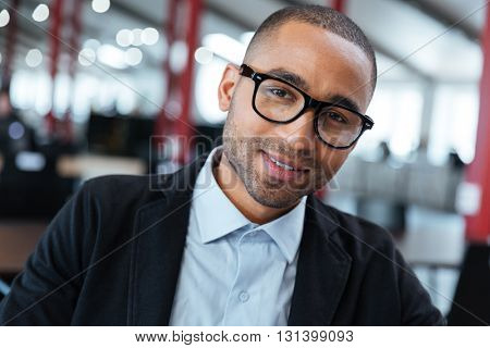Close-up  portrait of a smiling businessman in glasses at the office