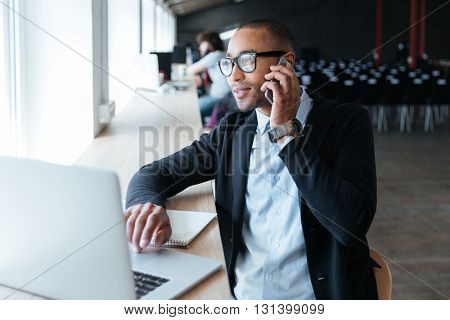 Businessman talking on the phone and working using laptop computer in the office