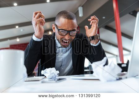 Shouting tired businessman at his desk at the office