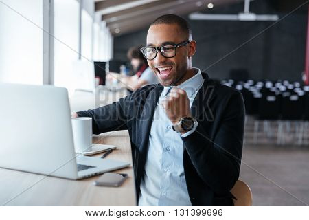 Handsome young businessman sitting at his ddesk, celebrating success with arms raised while looking at his laptop screen