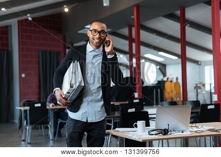 Smart young businnessman talking on the smartphone and carrying folders in the office