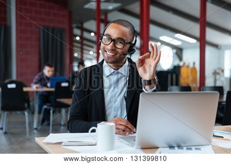 Businessman wearing headphones and showing okay sign at the desk