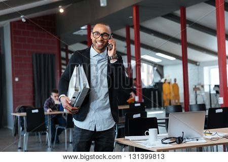 Young businessman talking on the cellphone and carrying binders in the office
