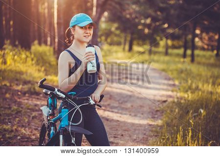 Young happy woman on bike standing on a hill road enjoying beautiful view summer sunny day resting drinking water