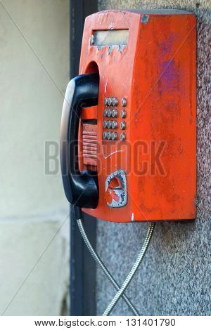 the big old payphone of red color a closeup and located outdoor on a wall