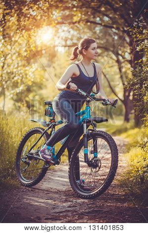 Happy woman cyclist rides in the forest on a mountain bike. Adventure travel. wide angle
