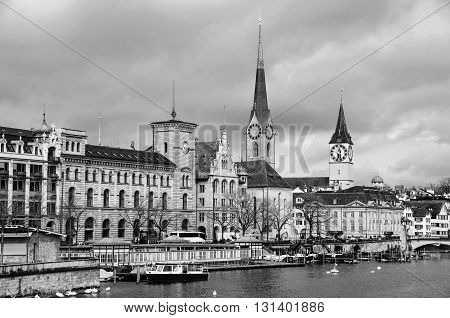 St. Peter Church and old Clock tower is one of the symbols of the city and major touristic attraction in Zurich, Switzerland. Limmat river with moored boats. Black and white