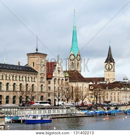 St. Peter Church and old Clock tower is one of the symbols of the city and major touristic attraction in Zurich, Switzerland. Limmat river with moored boats