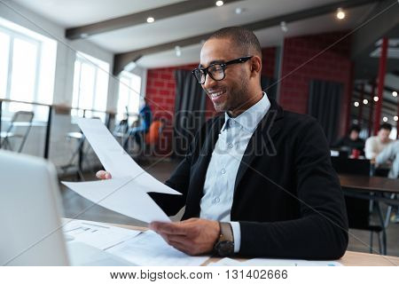 Handsome businessman looking at documents in his hands