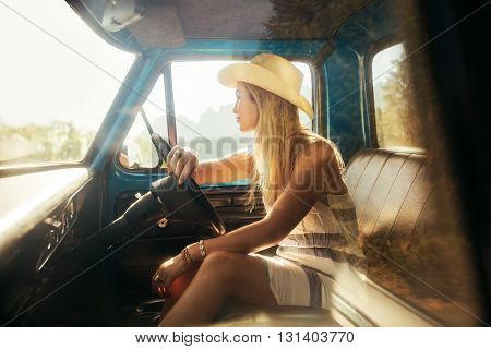 Portrait of young woman sitting on driving seat of a car and looking away. Girl wearing hat on a road trip.
