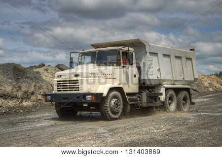 Poltava Region Ukraine - June 26 2010: Dump truck driving along the opencast road with mud