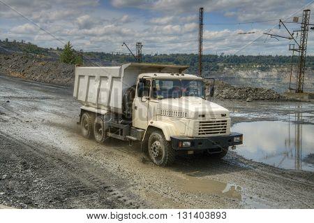 Poltava Region Ukraine - June 26 2010: Dump truck driving along the muddy road on the opencast