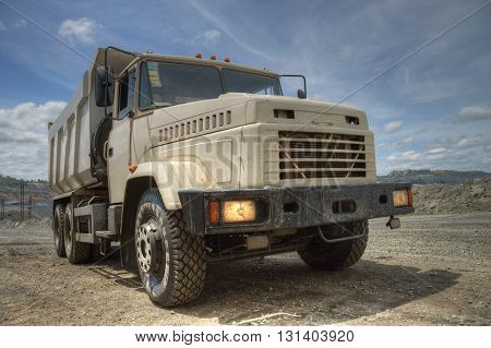 Poltava Region Ukraine - June 26 2010: Dump truck with headlights on waiting for loading on the iron ore opencast