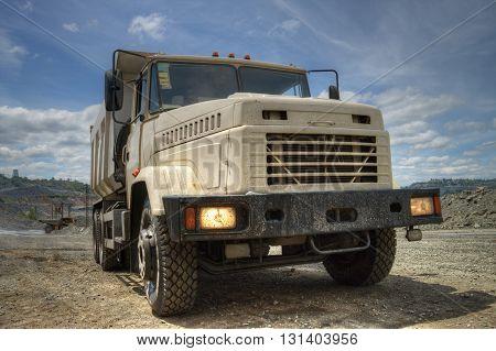 Poltava Region Ukraine - June 26 2010: Dump truck with headlights on waiting for loading on opencast