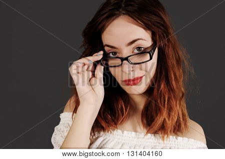Beautiful red haired woman is looking through her glasses with an innocent smile. Studio shot with dark background.