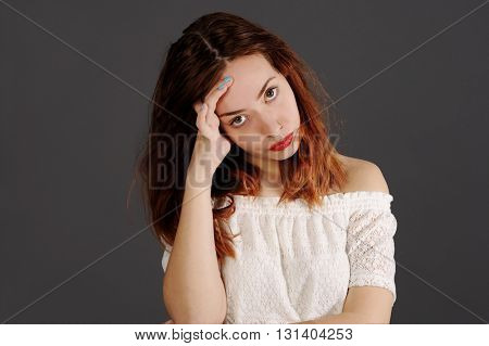 young red woman is looking depressed into the camera. Studio shot with grey background.