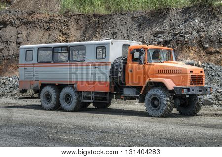 Poltava Region Ukraine - June 26 2010: Mining crew bus on the iron ore the opencast - side view