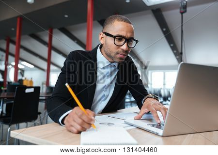 Young concentrated employee looking at computer monitor and noting during working day in office