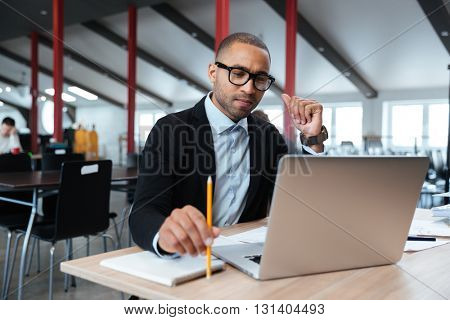 Serious businessman working with laptop in the office, holding pencil