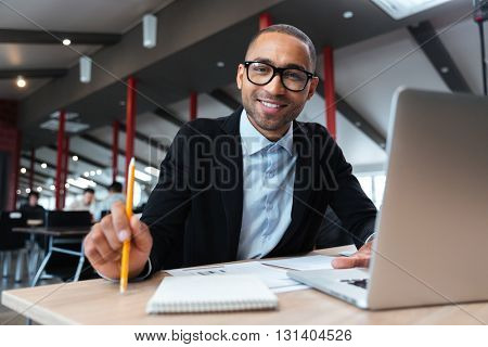 Businessman smiling at the working place and holding pencil