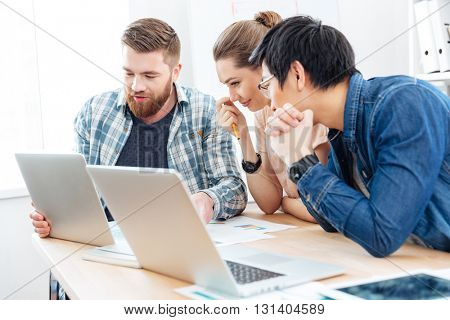 Three young businesspeople working for the project using laptops in office together