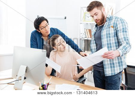Three concentrated young businesspeople working with documents and using computer in offie together