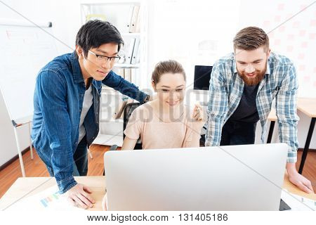 Smiling young woman and two handsome men working with computer in office together