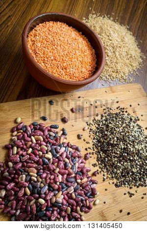 Lentils, red beans and brown rice on a wooden table and board