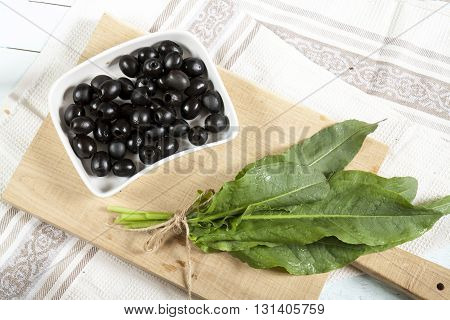 Black Olives And Green Sorrel On Light Wooden Board