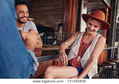 Smiling young caucasian woman wearing hat sitting at a coffee shop with her friends. Young people sitting at a cafe table and having fun.