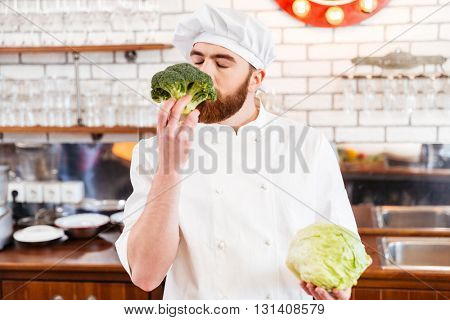 Happy bearded chef cook smelling fresh broccoli on the kitchen