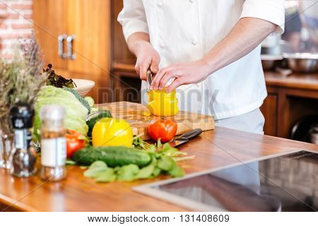 Closeup of professional chef cook in white uniform standing and cutting fresh yellow bell pepper on the kitchen