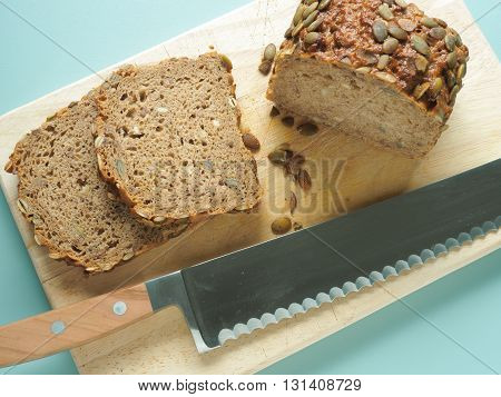 Whole grain pumpkin bread with a big knife in a kitchen