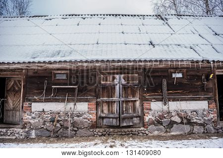 Old wooden byre covered with snow in Poland
